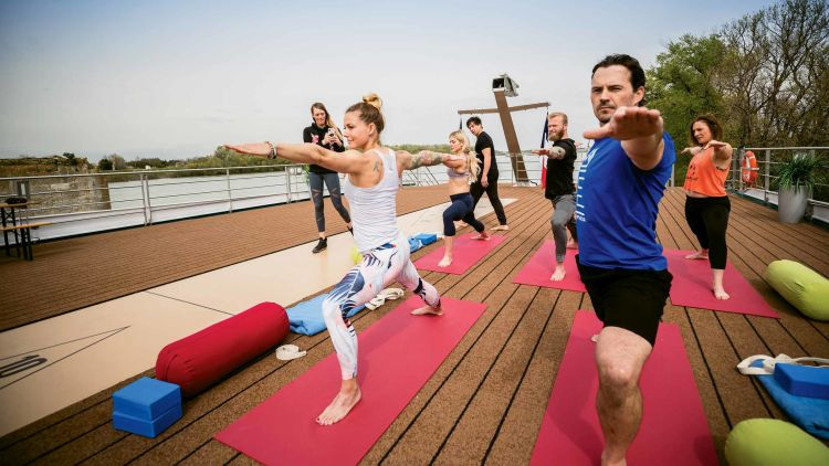 Fitness guru Christmas Abbott (in white tank top) practices yoga on the Amadeus Provence.