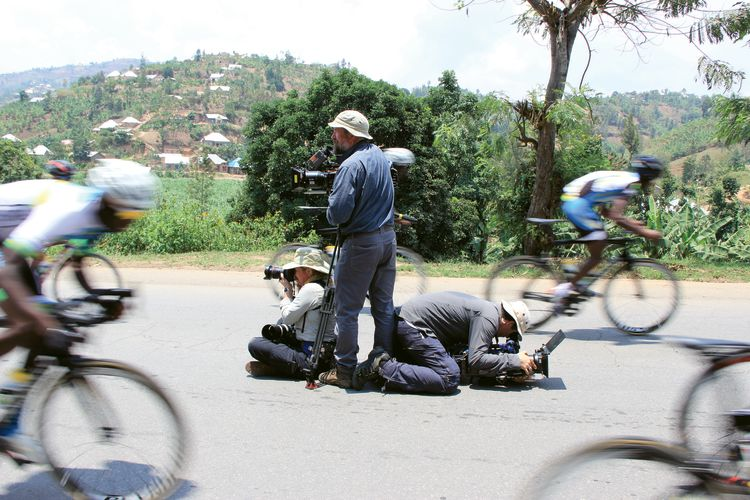 """The Royal Tour"" camera crew takes position in the middle of a road to shoot the Rwanda national cycling team zooming past."