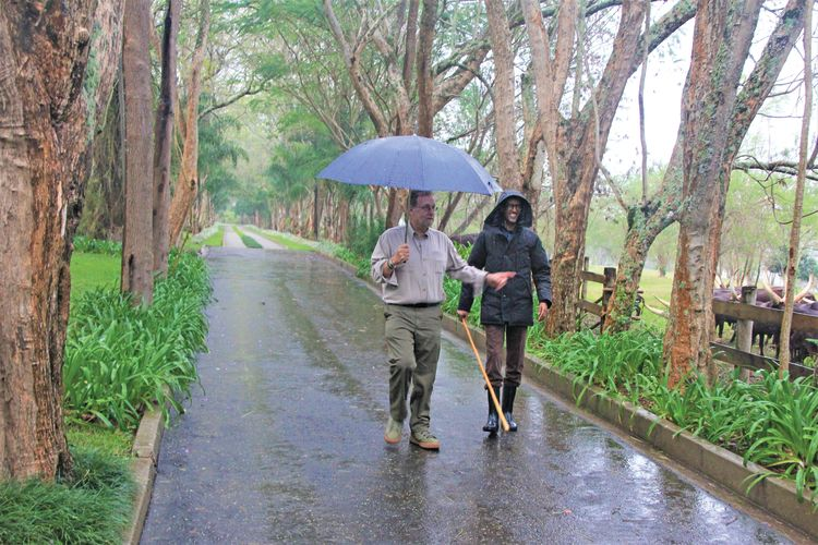 Their planned tennis match rained out, Greenberg and the president stroll to see cattle at his retreat, Muhazi.
