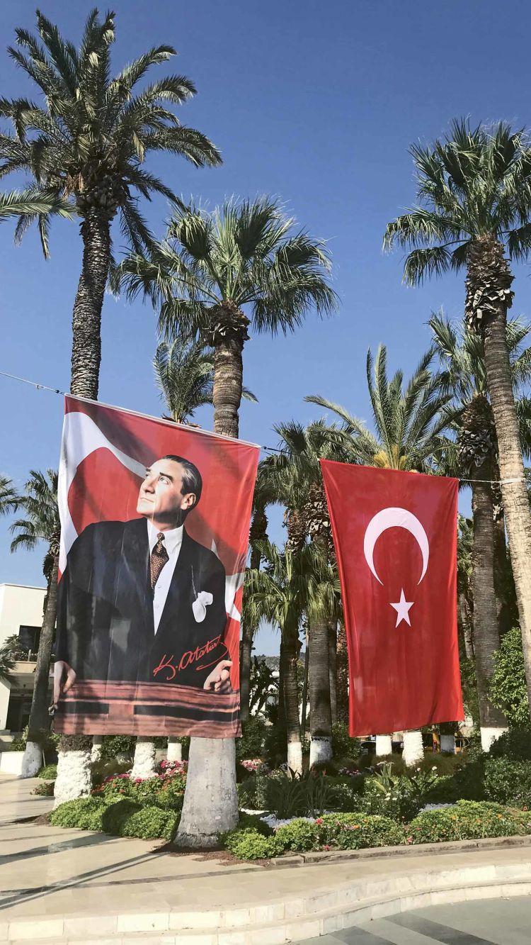 A banner showing Mustafa Kemal Ataturk, the father of the Republic of Turkey, flies alongside the national flag in the town square in Bodrum.
