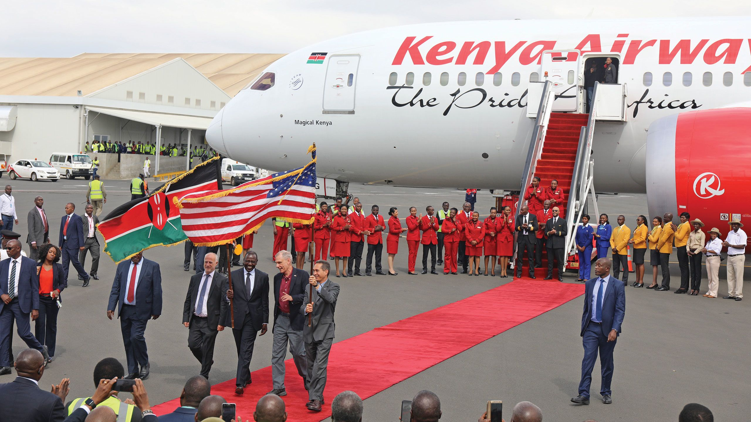 Kenya's deputy president William Ruto, center, U.S. ambassador to Kenya Robert Godec, in a red shirt, and Kenya Airways chairman Michael Joseph, left of Ruto, help celebrate the first nonstop commercial flight between the U.S. and Kenya at Nairobi's Jomo Kenyatta Airport in October. Photo courtesy of Kenya Tourism Board