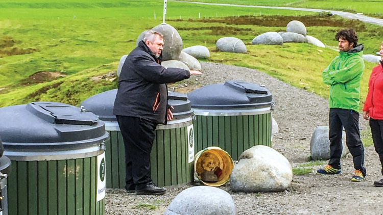 Eldar Andersen with the new industrial-strength garbage cans the Uttakleiv village has installed to cope with the garbage tourists generate. Photo by William Nash