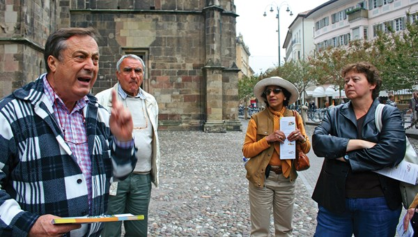 An animated local tour guide in Bolzano, Italy, with a Trafalgar tour director looking on.