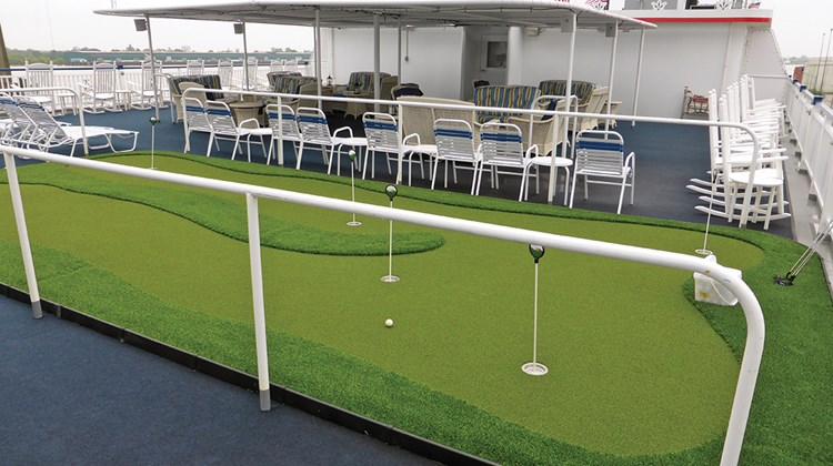 The outside spaces on Deck 5 have a shaded area with banks of cushioned chairs and settees as well as a putting green.