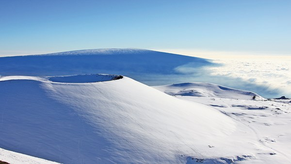 The snowy Mauna Kea summit on the Big Island. In the foreground is Mauna Loa.