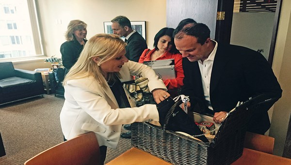 Celebrity Cruises CEO Lisa Lutoff-Perlo and Expedia CruiseShipCenters President Matthew Eichhorst with a picnic basket given to executives at the line's top accounts. Celebrity Associate Vice President Carol Cabezas looks on.