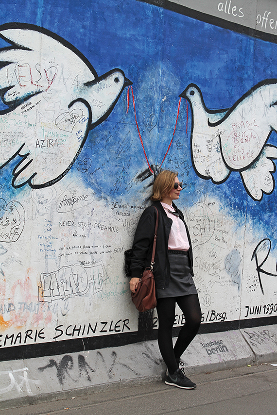 Along the Spree River, a woman poses at the East Side Gallery, the longest remaining section of the Berlin Wall. Photo Credit: JoAnna Haugen