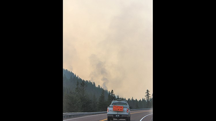 Cars along Highway 2 on the park's border had to travel in a caravan behind a pilot car through areas closest to the fires.