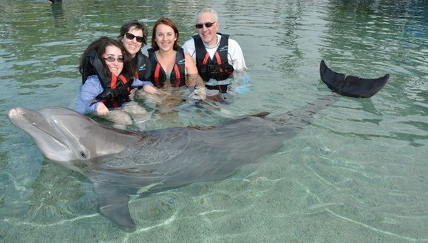 Rebekah Lovitt, left, whom Make-a-Wish flew free to Hawaii with the help of Alaska Air's Charity Miles program, swam with the dolphins at the Hilton Waikoloa Village on the Big Island.