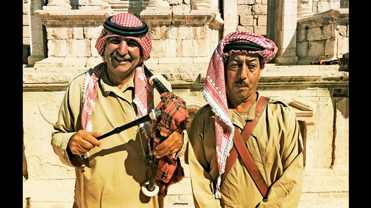 A couple of local bagpipe players perform for tourists in an ancient Roman theater in Jerash.
