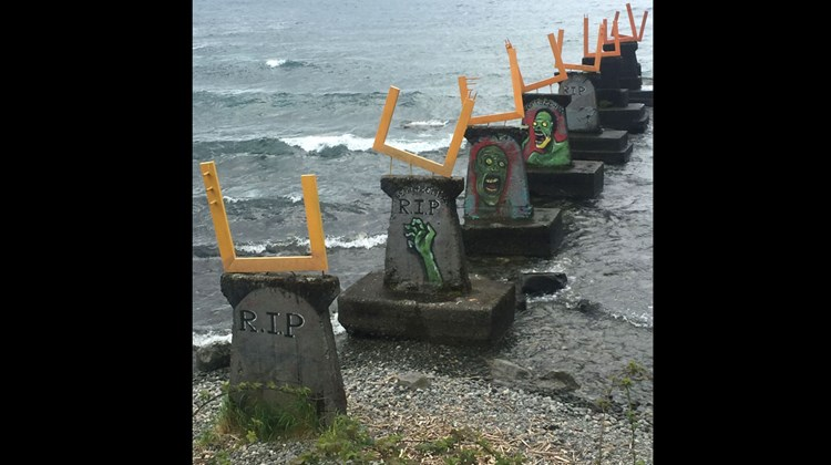 It was unclear whether the artist or a graffiti artist first recognized these shapes as tombstones in this Puerto Varas lakefront sculpture.