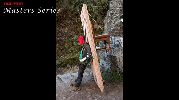 A Sherpa carrying building supplies and a chair rests on the Himalayan trail.
