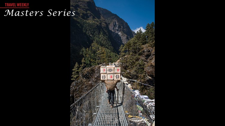 A Sherpa crosses a suspension bridge in the Himalayas on the way to Namche Bazaar.