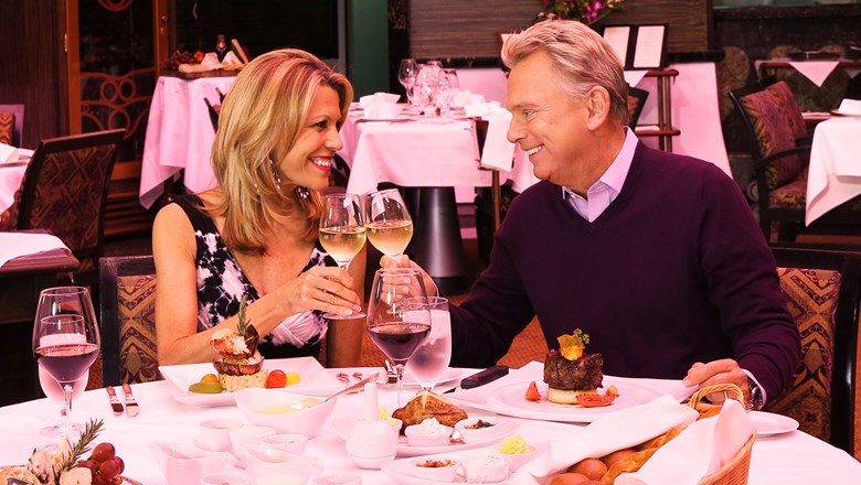 """Wheel of Fortune"" hosts Vanna White and Pat Sajak in the steakhouse on a Carnival ship."
