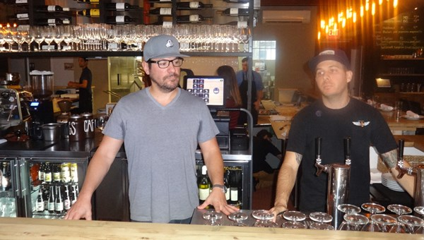 Rooster & The Till co-owner Ty Rodirguez, left, stands with an employee in front of the restaurant's open bar and kitchen.