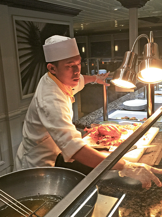 A chef on the Azamara Journey carves tandoori chicken on Indian Night at the Windows Cafe.