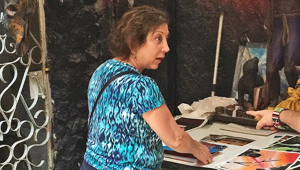 Agent Denise Kahoud of Pisa Brothers in New York looks through prints at the Callejon Hamel community art project in Havana.