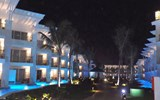 Resort accommodations bathed in blue light at night.