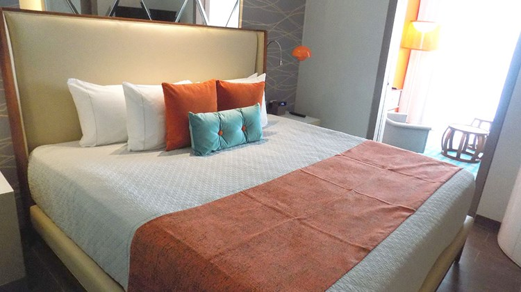 A king bed in a swim-up suite, accented with bright orange and aqua throw pillows, reminding guests that this is a Nickelodeon resort.