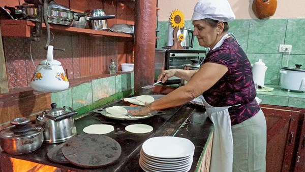 In Costa Rica, Dona Mara Rojas Perez cooks tortillas, handmade by a tour group during an in-home cooking class.