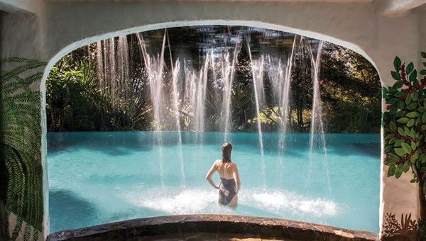 A guest stays cool under the waterfall at the Finca Rosa Blanca Coffee Plantation and Inn, located in the central valley mountain highlands above Costa Rica's capital of San Jose.