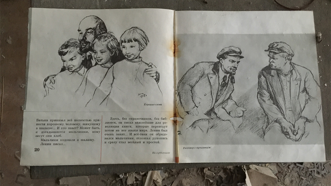 A schoolbook featuring images of Soviet revolutionary Vladimir Lenin, on the floor of the town's abandoned school. Photo Credit: Arnie Weissmann