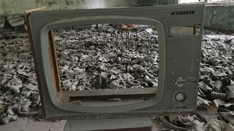Gas masks that were being stored in a Pripyat school lay strewn over the floor of the cafeteria, partially framed by a tubeless television.<br /><br /><strong>Photo Credit: Arnie Weissmann</strong>
