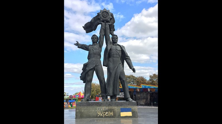 A statue in Kiev depicts Russian and Ukrainian workers holding the Soviet Order of Friendship of Peoples. The flag painted on the pedestal is that of modern Ukraine, and the government plans to replace it and nearby Soviet-era statues of friendship with a memorial dedicated to veterans of the present-day Russian-Ukraine War.<br /><br /><strong>Photo Credit: Arnie Weissmann</strong>