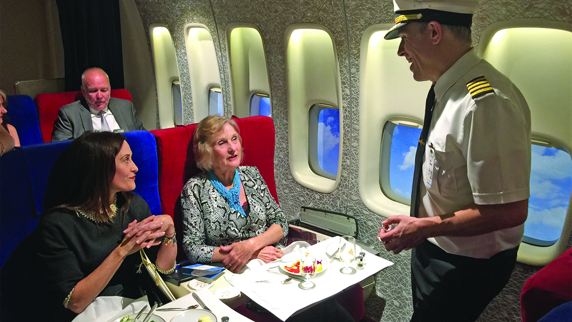 Anthony Toth, co-creator of the Pan Am Experience, talks with passengers Courtenay Taylor, left, and Maureen Taylor, a former Pan Am stewardess, in first class. Photo Credit: Robert Silk