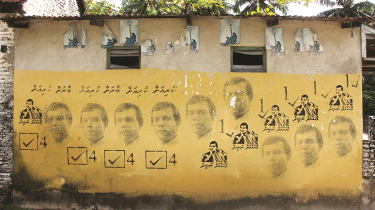 A wall covered in stencils with the image of exiled former president Mohamed Nasheed. Although Nasheed was deposed in a coup and initially jailed (he now lives in London), his Maldivian Democratic Party is still active, particularly on islands away from the capital, Male.<br /><br /><strong>Photo Credit: Arnie Weissmann</strong>