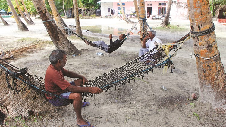 A hammock-culture prevails on Fiyoaree, where some men retreat from the midday sun to pass the time under the shade of palm trees.<br /><br /><strong>Photo Credit: Arnie Weissmann</strong>