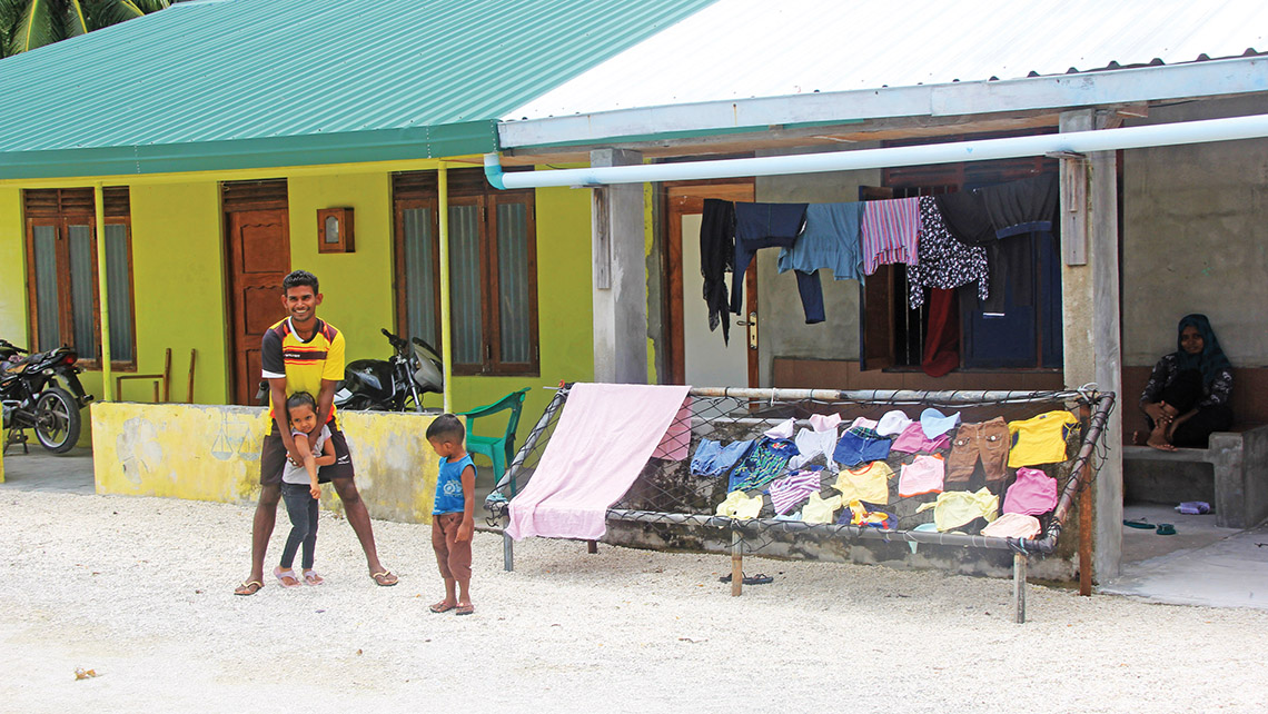 Laundry day: A father and his two children in front of their home after laying out their clothes on the island of Nadalla, as their mother watches from the shade of their porch. Photo Credit: Arnie Weissmann