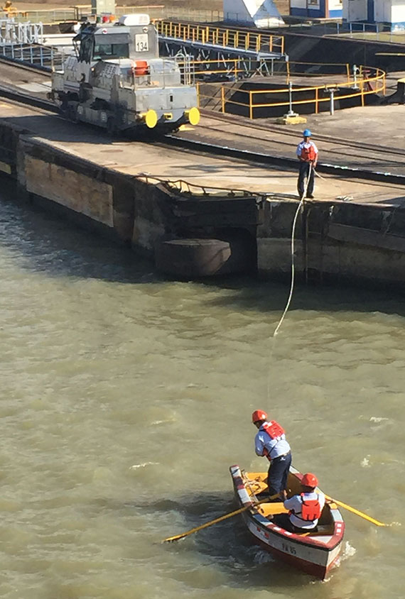 Workers use a rowboat to deliver a towline to ships going through the locks. The lines are attached to the mule in the background. Photo Credit: Tom Stieghorst