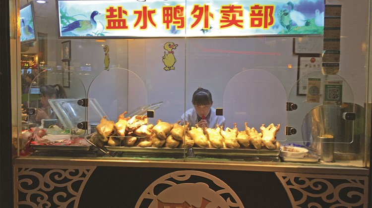 A local meal seems to invariably include duck, the local specialty, in all forms. Here, a street vendor sells salted duck.