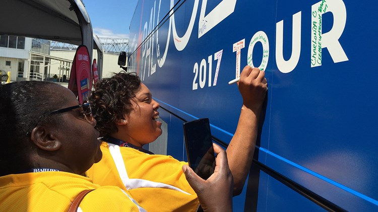 Violet Smith, of Gumbeaux Getaways in New Orleans, signs the Agentpalooza bus while fellow agent Tennille Harrison observes.<br /><br /><strong>Photo Credit: TW photo by Tom Stieghorst</strong>