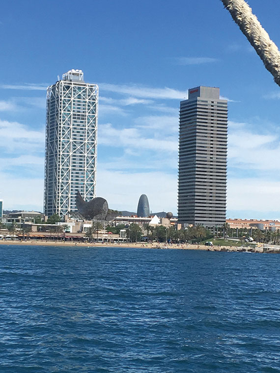 "Frank Gehry's fish sculpture, ""Peix,"" sits in front of the Mapfre Tower on Barcelona's waterfront; the tower on the right is the Hotel Arts."
