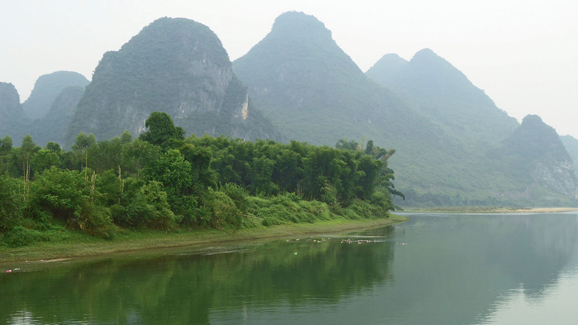Karst formations emerge from the mist along the Li River near Hangshuo. Photo Credit: Roger Allnutt