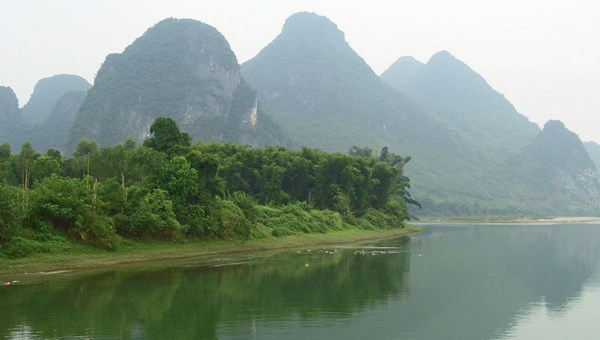 Karst formations emerge from the mist along the Li River near Hangshuo.