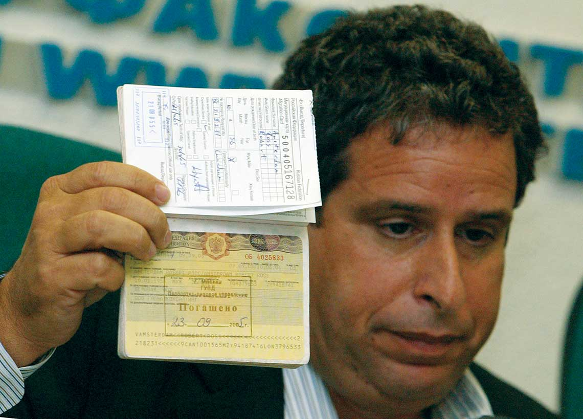 Robert Amsterdam, Canadian attorney for Russian oil tycoon Mikhail Khodorkovsky, shows his passport with his Russian visa annulled at a news conference in Moscow in September 2005. A group of Russian Federal Security Service officers had arrived at Amsterdam's hotel room in the middle of the night and taken away his passport, he said. When they returned the passport, his Russian visa had been annulled, and he was ordered to leave the country. Photo Credit: Mikhail Metzel/AP