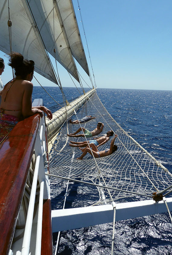 Star Clipper passengers lounge on the rigging beneath the bowsprit.