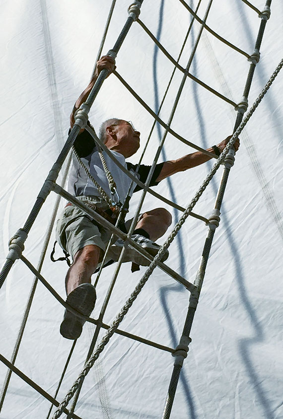 A guest climbs rigging to reach a platform on the ship's foremast. Photo Credit: TW photo by Tom Stieghorst