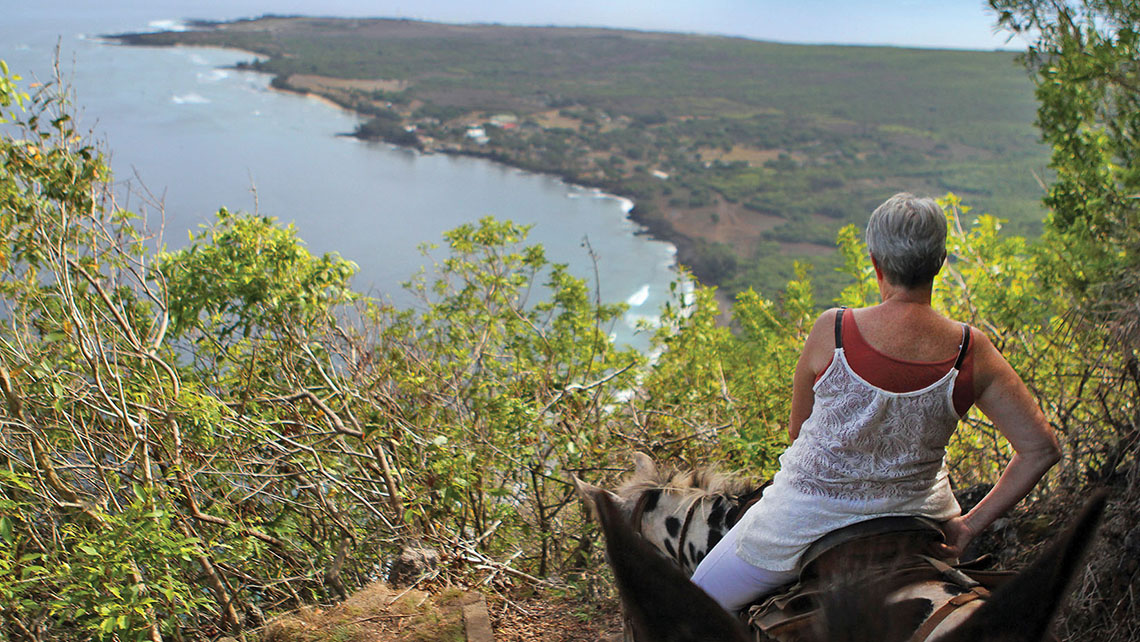 A visitor takes in the view of Kalaupapa below as she makes her way down the steep trail on a mule. Photo Credit: Tovin Lapan