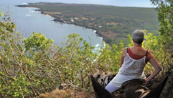 A visitor takes in the view of Kalaupapa below as she makes her way down the steep trail on a mule.