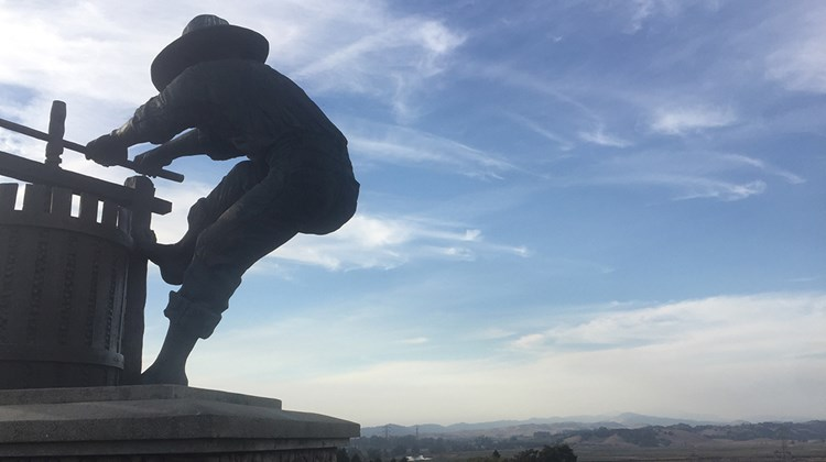 A statue of a man crushing grapes overlooks the Napa Valley, which was relatively clear and smoke-free on Monday, Oct. 16.