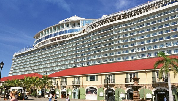 The Harmony of the Seas looms over the buildings of the shopping village at the cruise port in Falmouth, Jamaica.