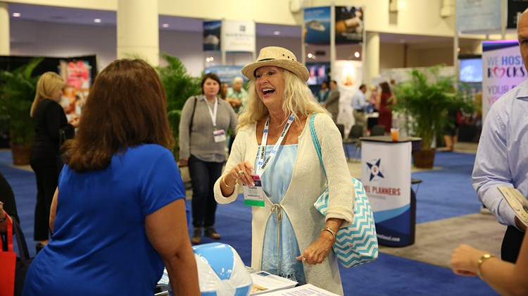 Travel adviser Virginia Accetta makes the most of the Exhibitor Showcase.<br /><br /><strong>Photo Credit: Creative Focus</strong>