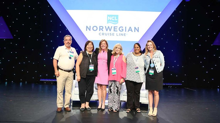 Camille Olivere, senior vice president of sales for Norwegian Cruise Line, poses with winners of sailings on the Norwegian Bliss, drawn during Friday's lunch.