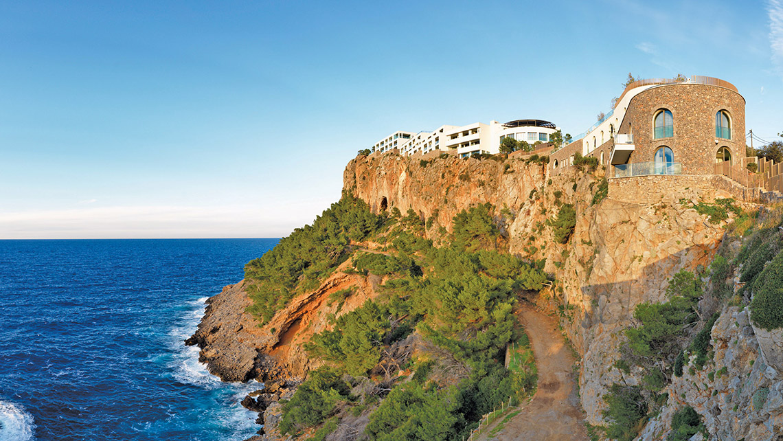 The Jumeirah Port Soller Hotel & Spa, built on a cliff in Mallorca, offers stunning views of the Mediterranean and the island's rugged terrain.