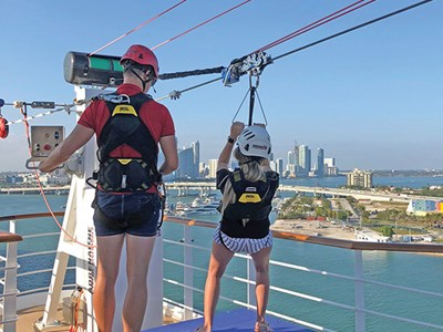 A rider prepares to launch on the longest zipline at sea, onboard the MSC Seaside.
