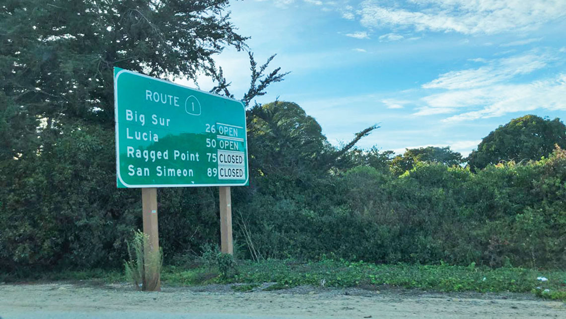 A sign alerts drivers to closed roads along Highway 1.